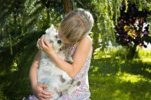 kind knuffelt klein hondje in gras