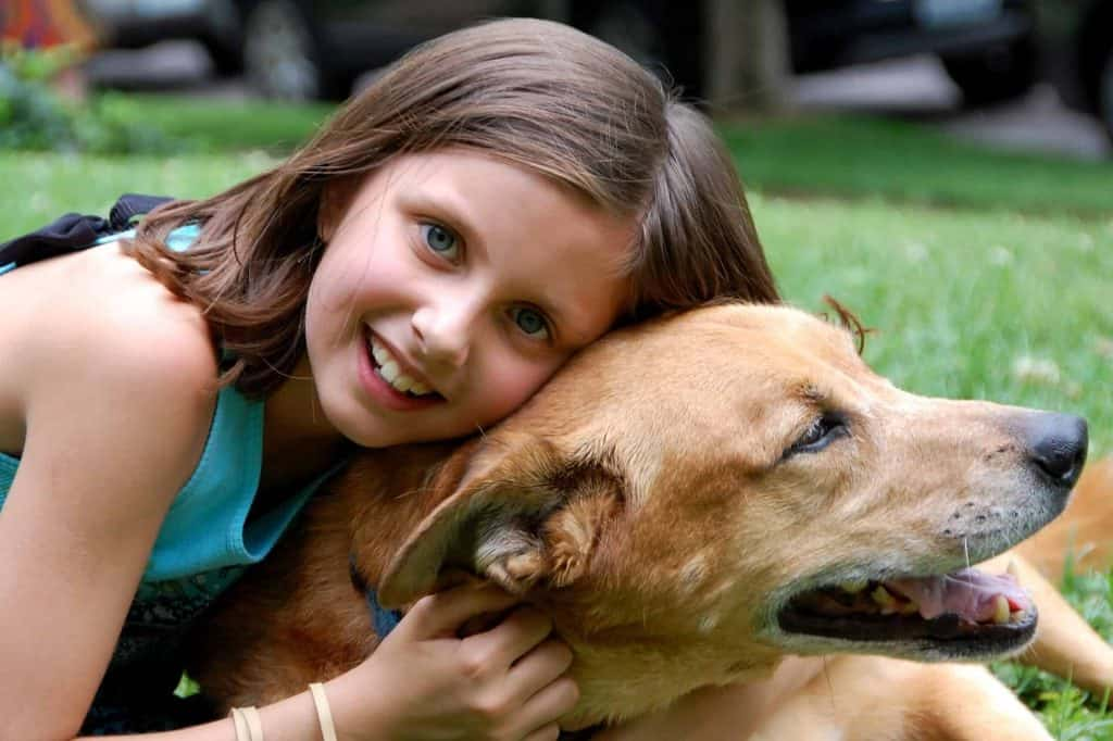 kind knuffelt hond in het gras
