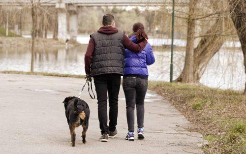 man en vrouw laten een hond uit