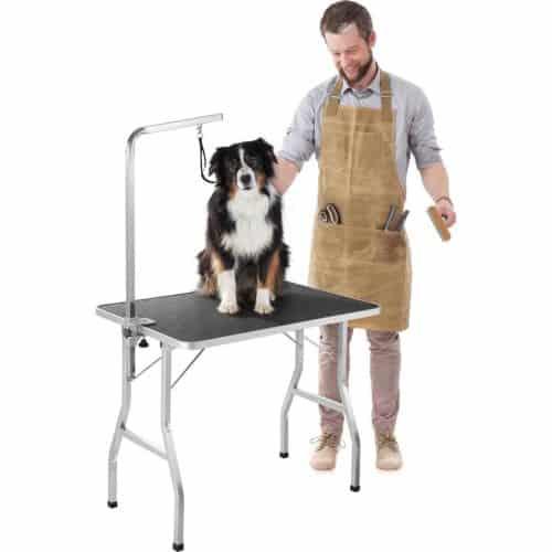 man trimt een hond op een trimtafel